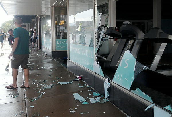 Large glass windows at The Chiropractic Center exploded as heavy rain and hail moved through downtown Enid during the AMBUCS Twilight Criterium bicycle races Saturday, August 16, 2014. Races were delayed as AMBUCS members removed debris from the sidewalk and street and reset the road barriers. (Staff Photo by BONNIE VCULEK)