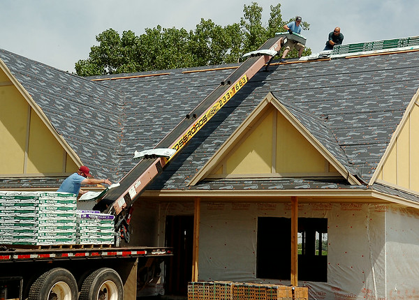 Ryan Beckham (bottom left) loads shingles onto a conveyor belt as workers position the materials on the roof of a new home in Chisholm Creek Village Wednesday, August 27, 2014. (Staff Photo by BONNIE VCULEK)