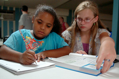 Shakara Revels, a third-grade student in Enid Public Schools, receives help from Kimberly Raymond during the Zoe Bible Church Kid's Cafe mentoring program Wednesday, August 27, 2014. The non-profit, Christian-based activities are offered Monday-Friday from 3:30-6 p.m. at 729 E. Maine. (Staff Photo by BONNIE VCULEK)