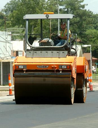 A heavy equipment operator uses an asphalt roller along Broadway Friday, August 01, 2014. (Staff Photo by BONNIE VCULEK)