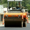 A heavy equipment operator uses an asphalt roller along Broadway Friday, August 01, 2014. (Staff Photo by BONNIE VCULEK)
