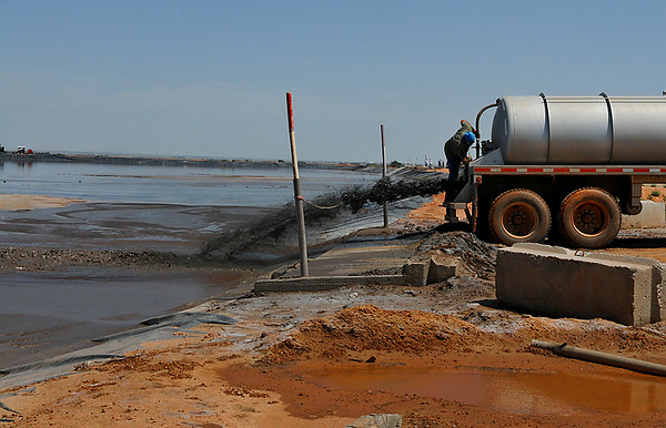 A driver empties a tanker of drilling mud into one of the mud pits at Gray Mud Disposal near Hillsdale Tuesday. (Staff Photo by BILLY HEFTON)