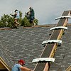 Roofers carry shingles across the ridge of a new home in Chisholm Creek Village Wednesday, August 7, 2014. (Staff Photo by BONNIE VCULEK)