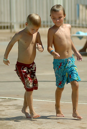 Henson Reames and Matt McDaniel walk quickly on the hot cement as they enjoy an afternoon at Splash Zone Saturday, August 9, 2014. (Staff Photo by BONNIE VCULEK)