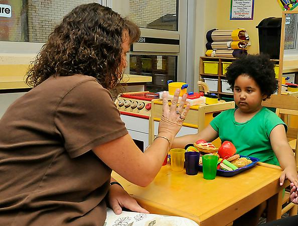 Jasmine Gordon works with kindergarten teacher, Annemarie Miller, during Meet the Teacher night at Monroe Elementary Monday. (Staff Photo by BILLY HEFTON)
