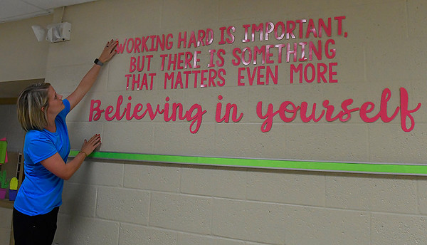 Katie Gonzalez, fourth grade teacher at Monroe Elementary, straightens letters of the motto she has on the wall outside her classroom Tuesday August 15, 2017. (Billy Hefton / Enid News & Eagle)