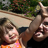 A Monarch butterfly clings to the thumb of Arielle Reed as she sits on her mother's lap, Darian Reed, August 29, 2017 at Dillingham Garden. (Billy Hefton / Enid News & Eagle)
