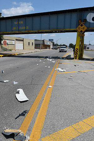 Debris litters east Maine street after a 5th wheel travel trailer struck the railroad bridge Thursday August 3, 2017. (Billy Hefton / Enid News & Eagle)