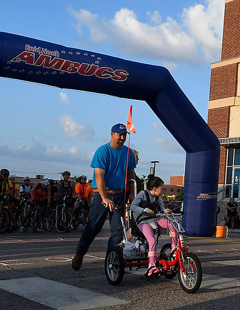Jeremiah Benson pushes his daughter, Hosanna, in her amtryke at the start the 12th annual Tour de Trykes in downtown Enid August 19, 2017. (Billy Hefton / Enid News & Eagle)