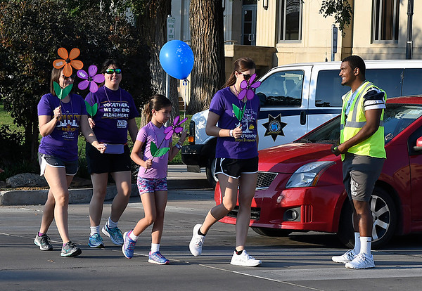Enid Plainsmen's Ivey Mace helps to control traffic during the Walk to Enid Alzheimer's Friday August 4, 2017 in downtown Enid.  More than 300 walkers took part in the event that raised almost $50,000. (Billy Hefton / Enid News & Eagle)