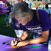 Liz Breitenkamp from the Enid Elks Lodge write the name of a loved one on a promise flower before the start of the Walk to Enid Alzheimer's Friday August 4, 2017 in downtown Enid. More than 300 walkers took part in the event that raised almost $50,000. (Billy Hefton / Enid News & Eagle)