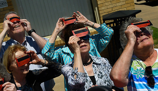 A group of residents from The Commons look at the solor eclipse through solar viewers at the NOC Enid Astronomy Complex August 21, 2017. (Billy Hefton / Enid News & Eagle)
