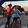 Becca Cook helps Kristafer Murphy with his helmet prior to the start of the 12th annual Tour de Trykes in downtown Enid August 19, 2017. (Billy Hefton / Enid News & Eagle)