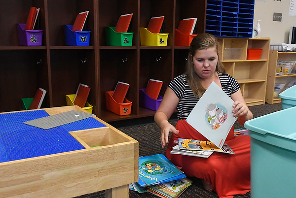 Ainsley Hoover sorts through books as she prepares her kindergarten classroom at Garfield Elementary for the first day of school. Classes begin at Enid Public Schools August 15. (Billy Hefton / Enid News & Eagle)