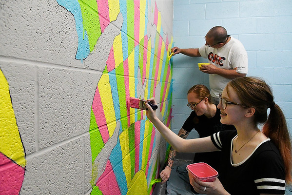 """(Front to Back) Lilian Kaiser, Cammeron Kaiser and Dane Tate paint the mural """"Sunshine Felines"""" Saturday August 18, 2018 at the Enid Animal Control building. The mural, that was designed by Kelly Tompkins, is part of the overall remodel of the cat room. The finished room will be called """"The Cat Corner."""" and will allow cats available for adoption to be put in the room and act as a space for people to interact and play with the cats to see if they want to adopt them. """"Cats tend to be healthier, more adoptable and happier if they have a place to play,"""" said Enid Animal Control Adoption Coordinator Charlet Ringwald. (Billy Hefton / Enid News & Eagle)"""