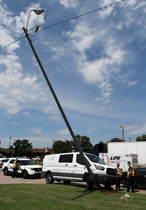 A lightpole is held up by a wire after being hit by a van that was involved in a multi vehicle accident in front of the Sonic on west Willow Tuesday, August 27, 2019. (Billy Hefton / Enid News & Eagle)