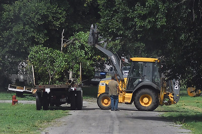 A backhoe is used to lift down tree limbs into a truck in Ames Tuesday, August 13, 2019 after strong storm moved through the area Monday.. (Billy Hefton / Enid News & Eagle)