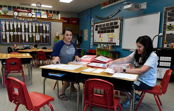 Kara Ball (right) and Ciera Rice put together folders at Chisholm Elementary Friday August 9, 2019. Chisholm schools begin classes August 14, 2019. (Billy Hefton / Enid News & Eagle)