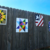 Barn quilts painted by Susan Wanzer hang on a fence at her home west of Drummond Wednesday, August 14, 2019. (Billy Hefton / Enid News & Eagle)