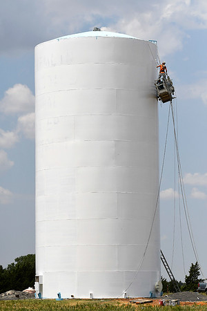 Painters work on a water tower along west Robertson Tuesday August 6, 2019. (Billy Hefton / Enid News & Eagle)