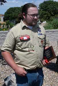 Hunter Mitchell holds a plaque presented to him by 4RKids in recognition of his Eagle Scout project of memorial flag garden at the 4RKids Putt Putt course. (Billy Hefton / Enid News & Eagle)