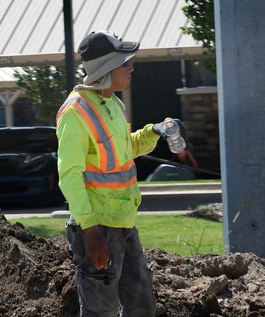 A construction worker grabs a quick drive while wotking on north Cleveland street Monday, August 19, 2019 as the temperature rose to over 100 degrees. (Billy Hefton / Enid News & Eagle)