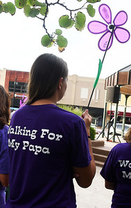 Maggie Base holds a purple flower for her papa, Oliver Hursh, at the Walk to End Alzheimer's Friday, August 2, 2019 on the Garfield County courthouse square in downtown Enid. (Billy Hefton / Enid News & Eagle)