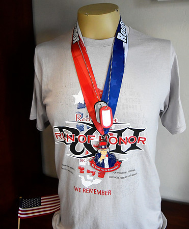 A tee shirt from the Red Dirt Run of Honor on display inside the M.L. Becker Learning Center at the Woodring Wall of Honor and Veterans Park. The run was one of the event sited in the award. (Billy Hefton / Enid News & Eagle)