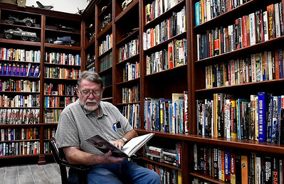 Steve Wilson thumbs through a book in the reference library of the M.L. Becker Learning Center at the Woodring Wall of Honor and Veterans Park. (Billy Hefton / Enid News & Eagle)