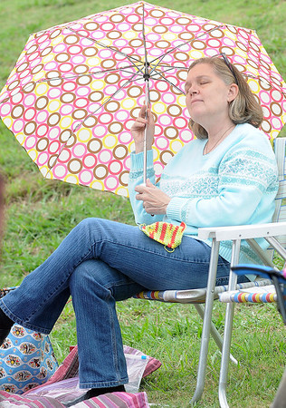 Holly Baker, from Tulsa, relaxes under an umbrella as she listens to the musicians perform during Fling at the Springs Saturday at Government Springs Park. (Staff Photo by BONNIE VCULEK)