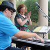 Amy Swanner applauds as Steven Harwood performs a musical medley on the keyboard as the duo open the Fling at the Springs Saturday at Government Springs Park. (Staff Photo by BONNIE VCULEK)