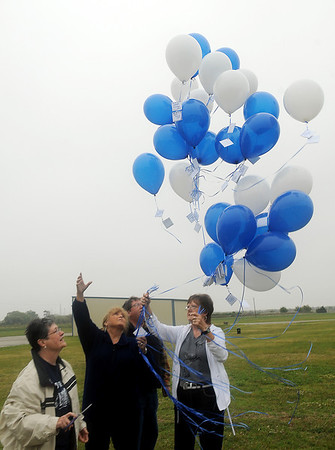 Four members of the Enid High School class of 1965 release blue and white balloons in honor of their classmates who have died Saturday during a special memorial service at the Woodring Regional Airport Wall of Honor. A packet of wild flowers was attached to each balloon with the name of a deceased class member. (Staff Photo by BONNIE VCULEK)