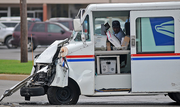 An Enid postman resorts the mail in his truck after colliding with a Toyota Tundra truck in the 700 block of N. Cleveland Saturday. Enid Police detoured local traffic into Sunset Plaza while officers worked the scene. (Staff Photo by BONNIE VCULEK)