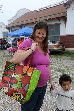 Char Thompson and her son, Ysrayl, leave Enid Farmers Market Saturday with a large bag of fresh vegetables. Enid Farmers Market will reopen next May. (Staff Photo by BONNIE VCULEK)