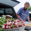 Evelyn Koehn, from Koehn Family Farm, offers home-grown radishes, squash and okra to the Enid Farmers Market shoppers Saturday. (Staff Photo by BONNIE VCULEK)