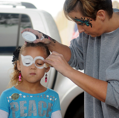 April Lumpkin (right), from C.A.T.'S Illusions, creates a design on Trinity Sletten Saturday during the Cherokee Strip Celebration festivities in Enid. (Staff Photo by BONNIE VCULEK)