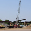 A crane lifts a section of steel from the bridge over US-64 Wednesday. Construction is scheduled to be completed after the first of the year. (Staff Photo by BILLY HEFTON)