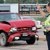 Enid Police Officer Bart Arnold directs traffic as a Stanley's Wrecker Service employee prepares a Ford Ranger for towing Thursday on the N. Van Buren overpass near Hughes Lumber. (Staff Photo by BONNIE VCULEK)