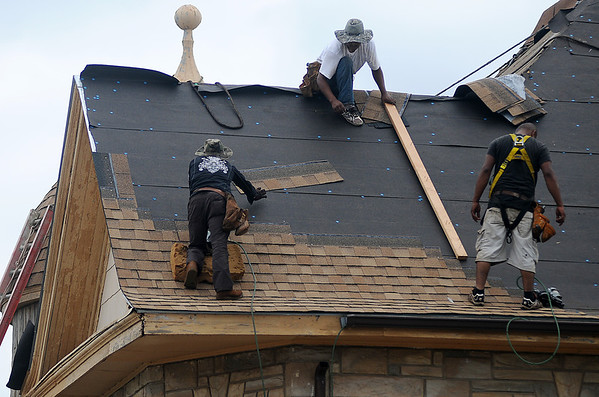 Daring roofers shingle the steep, second story roof of Stepping Stones Community Services at 701 W. Maine Friday. (Staff Photo by BONNIE VCULEK)