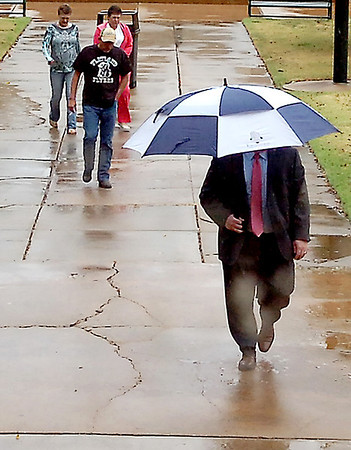 Visitors to the Garfield County Courthouse make their way through the rain Thursday. (Staff Photo by BILLY HEFTON)