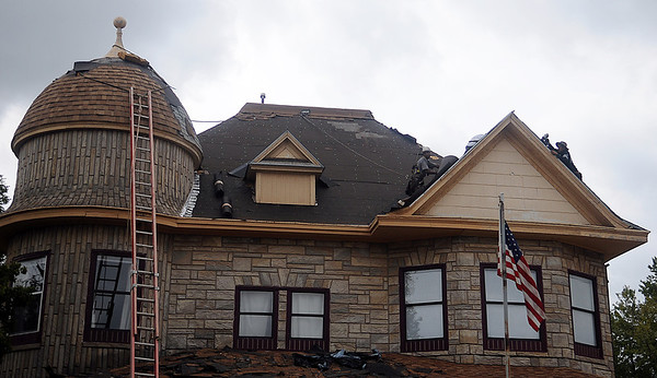 Daring roofers shingle the second story roof of Stepping Stones Community Services at 701 W. Maine Friday. (Staff Photo by BONNIE VCULEK)