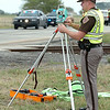 An Oklahoma Highway Patrolman uses a laser to measure the scene of a fatality accident Thursday on US 412 east of 78th street. (Staff Photo by BILLY HEFTON)