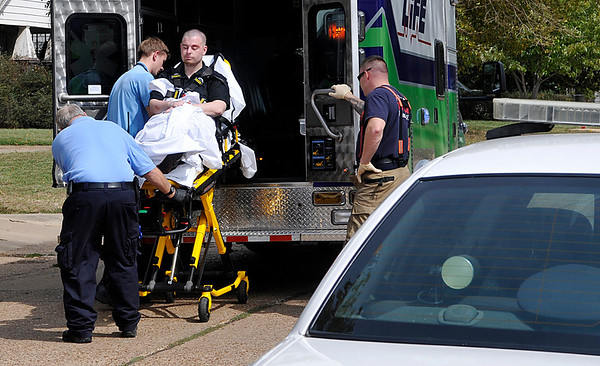 Emergency personnel load a stabbing victim into an ambulance Monday on east Cherokee. (Staff Photo by BILLY HEFTON)