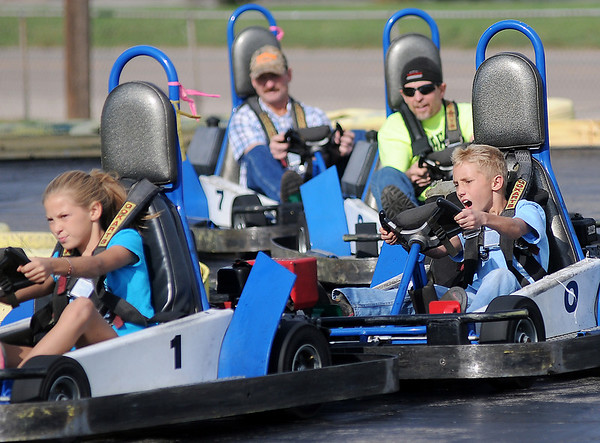 Brooklyn Owens, Kean Eck, Merrill and Darrell Eck (first-fourth places) are bumper to bumper as they round a sharp curve at Comet Go Carts Sunday. (Staff Photo by BONNIE VCULEK)