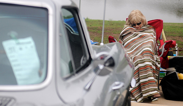 Jean Hendricks, from Oxford, Kan., tries to keep warm as she displays her 1964 Chevy Corvette Sting Ray Saturday during the American Garfieldi Car and Motorcycle Show at Meadowlake Park North. Proceeds from the event support the Vietnam Memorial Wall project. (Staff Photo by BONNIE VCULEK)