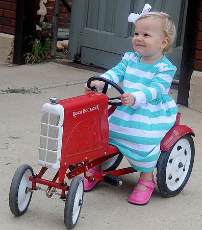 Olivia Brush enjoys her tractor ride at Enid Farmers Market Saturday. (Staff Photo by BONNIE VCULEK)