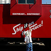 """Frank """"Watermelon"""" Campbell reaches high to paint around the letters on a caboose Saturday at the Railroad Museum of Oklahoma. (Staff Photo by BILLY HEFTON)"""