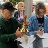 Lonnie Howerton, Ed D. (left), from ACCESS/East County Community Schools for the Orange County Department of Education in Santa Ana, CAL, rings a bell as Sue Strickler Dempsey read the names of their beloved classmates during an Enid High School class of 1965 memorial service at Woodring Municipal Airport Wall of Honor Memorial Saturday. (Staff Photo by BONNIE VCULEK)