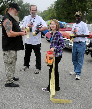 Ceara Johns sells 50/50 raffle tickets during the American Garfieldi Car and Motorcycle show Saturday at Meadowlake Park North.