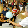 Gissela Ramirez receives free cotton candy from Deanna Chesser Sunday during Leonardo's Family Fun Festival at Leonardo's Discovery Warehouse and Adventure Quest. The event was free to the public as part of the Cherokee Strip Celebration festivities. (Staff Photo by BONNIE VCULEK)